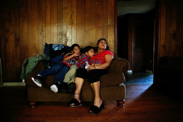 Morena Vasquez watch television with her son's Kevyn Rodriguez, 8, (L) and Isai Rodriguez, 5, at their home in Rome, Georgia