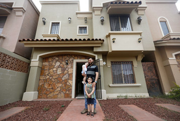 Hender Huerta, a Venezuelan living in Mexico poses with his two daughters outside of their house in Hermosillo