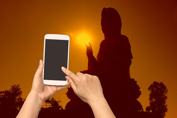 woman hand hold and touch screen smart phone on blurred religion sign.