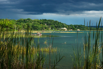 View on the village with dock along the lake shore with dark blue cloudscape, El Remate, Péten, Guatemala