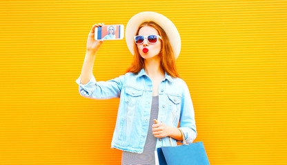 Cool girl takes a picture self portrait on smartphone in the city on a orange background
