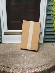 A brown package is left vulnerable at front door