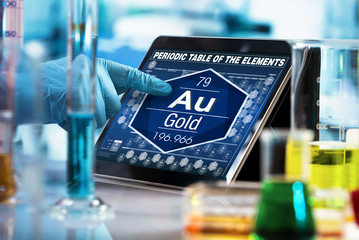 researcher working on the digital tablet data of the chemical element Gold Au / researcher consulting information on the computer of the periodic table of elements