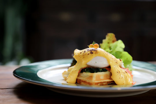 Breakfast food egg benedict , poached egg with yellow sauce with waffle and smoked salmon on wood background