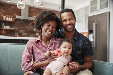 Portrait Of Family With Baby Daughter Relaxing On Sofa At Home Together