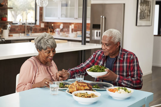 Senior Couple Enjoying Meal Around Table At Home