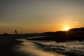 Man walks on the beach of Macaé Rio de Janeiro Brazil at sunrise