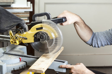 carpenter cutting with electric sawdust