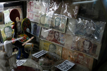Old Venezuelan bolivar notes are seen at a shop counter during a special inspection of Venezuelan soldiers to a municipal market in Caracas