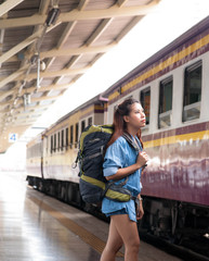 traveler walking alone with her backpack to train at train station
