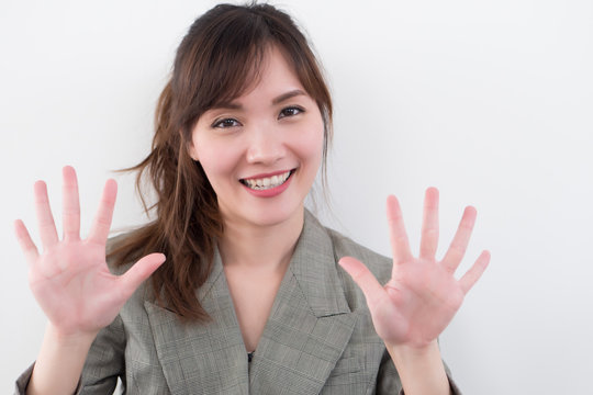 asian business woman pointing ten fingers, 10 points; portrait of positive happy smiling asian businesswoman pointing up ten fingers, 10 points number; asian chinese adult woman model business theme