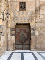 Wooden decorated copper plated door and stone bricks wall at the courtyard of Al-Sultan Al-Zahir Barquq mosque, Al-Moez Street, Old Cairo, Egypt