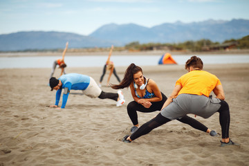 Group of young people is warming up before jogging on the beach by the sea