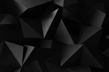 Macro image of black geometric shapes, three-dimensional effect, abstract background