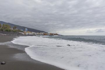 Puerto de la Cruz, Tenerife, Canary Islands - view of colorful houses, sea and volcanic-sand beach. Black beach in tenerife