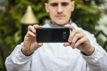 Парень фотографирует на черный телефон