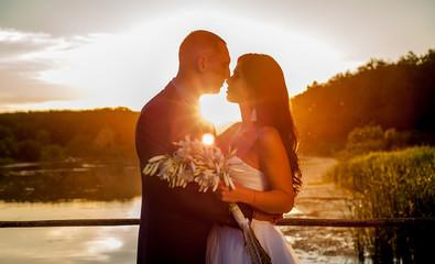 the bride and groom at sunset on the  bridge, kiss and hug, wedding day