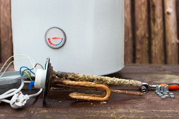 broken water heater with heating elements, on wooden background