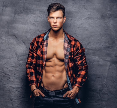 Sexy guy with unbuttoned fleece shirt posing at a studio.