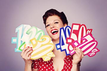 jolie femme pinup rousse souriante avec affiches soldes