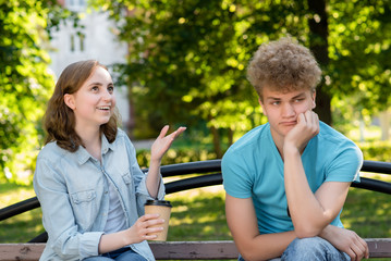 A guy with a girl in summer in a park in nature. The man is tired of talking. The girl continues to talk I do not want to listen. Emotional happily smiling and looking up.