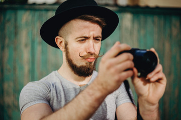Fashion photography, people,style, hobby, technology concept. Hipster man photographer taking pictures using modern camera.
