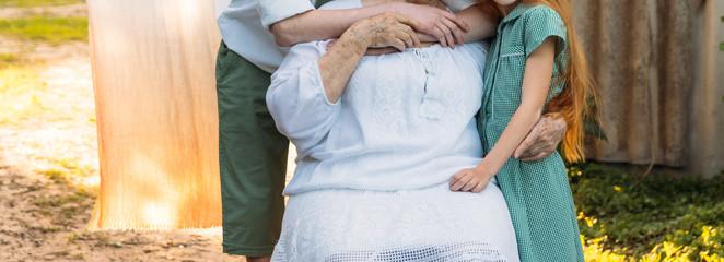 grandchildren, children hugging grandmother, elderly woman. meeting grandmother and grandchildren. grandmother embraces grandchildren, brother and sister. grandson and granddaughter came to visit.