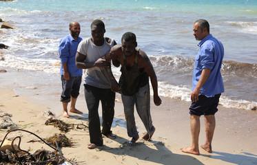 Migrants leave a boat at the coast of Tajoura, east of Tripoli