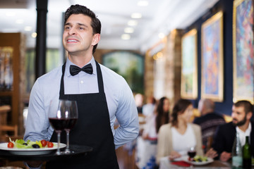 Smiling waiter with serving tray in restaurant