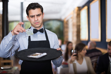 male waiter looking at a tip on a tray
