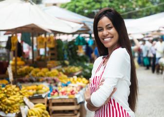 Beautiful latin american woman selling fruits at farmers market