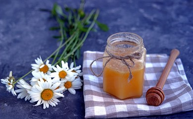 Honey in a jar and a bouquet of chamomiles