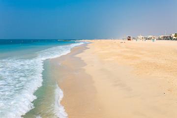 Panoramic view on nice Jumeirah beach in Dubai, UAE. United Arab Emirates famous tourist destination. Clear blue water Persian gulf, Indian Ocean