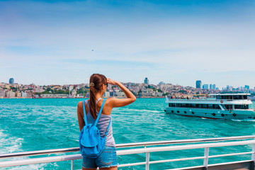 Young tourist woman in Istanbul. Panorama cityscape of famous tourist destination Bosphorus strait channel. Travel landscape Bosporus, Turkey, Europe and Asia.