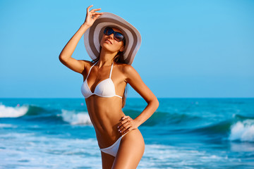 Portrait of sexy beautiful tanned woman posing in colorful swimwear bikini at the sea coast. Exotic country travel and rest concept. Slim figure and sexy body.