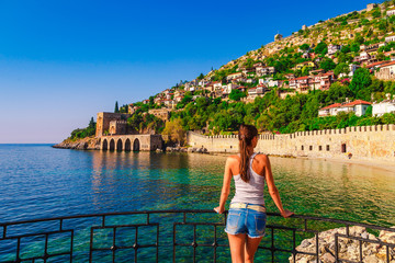 Young woman look on ancient shipyard from Kizil Kule tower in Alanya peninsula, Antalya district, Turkey, Asia. Famous tourist destination with high mountains. Part of ancient old Castle
