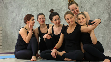 Group of girls in fitness class at the breaktaking selfie via cell phone, happy and smiling, show funny face