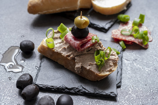 Bread with pate on the black slate tray decorated with black and green olives