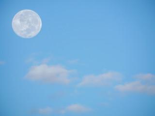 Dia ensolarado com céu azul com lua cheia ao canto.