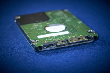 Close up of hard disk internal mechanism hardware on blue background