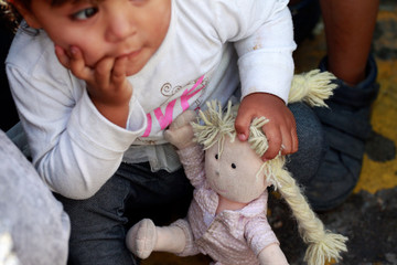 A member of a migrant family from Mexico, fleeing from violence, holds her doll while waiting to enter the United States to meet officers of the U.S. Customs and Border Protection to apply for asylum at Paso del Norte international border crossing bridge