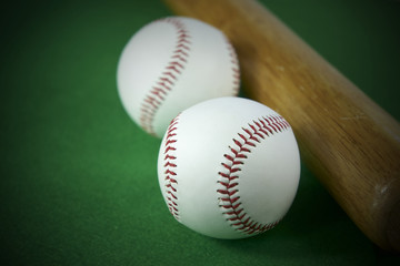 Two White Baseball ball and wooden bat isolated on green felt background