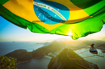 Photo sur Aluminium Brésil Brazilian flag shines above the golden sunset city skyline at Sugarloaf Mountain in Rio de Janeiro Brazil.