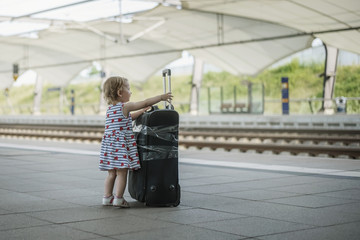 little sweet girl with a big suitcase on a deserted railway platform.