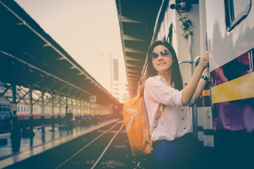 Girl wearing backpack waiting for a train. Traveling in Bangkok Thailand. Travel concept