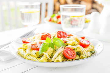Pasta with basil pesto, tomato and cheese on plate