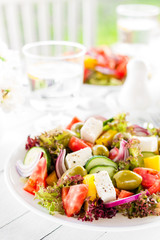 Greek salad. Fresh vegetable salad with tomato, onion, cucumber, pepper, olives, lettuce and feta cheese. Greek salad on plate on white table