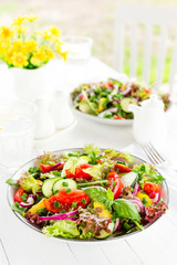 Fresh vegetarian vegetable salad with tomato, onion, cucumber, pepper, basil and lettuce. Salad on plate on white table