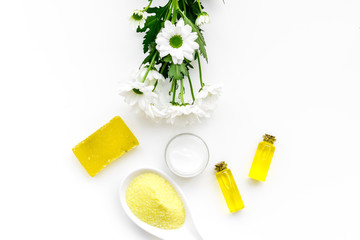 Chamomile spa cosmetics with natural herbal ingredients. Chamomile spa salt, soap, oil and cream on white background top view copy space