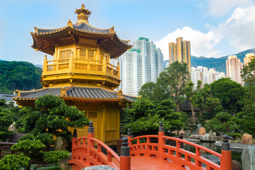 Golden Pagoda in Nan Lian garden, with red bridge and surrounded by green plants. The Hong Kong Skyline is in the background.